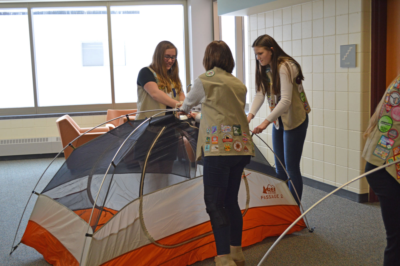 Three Girl Scouts build a tent together in the outdoor workshop.