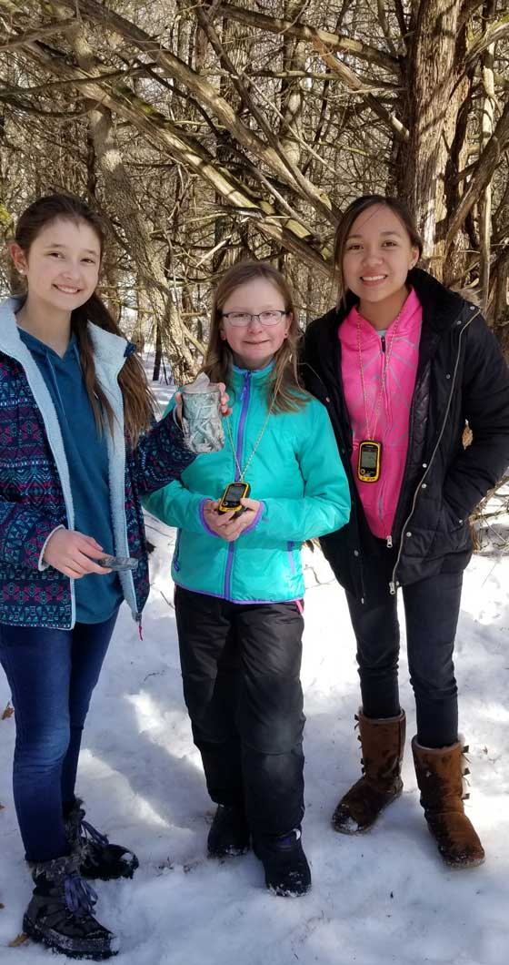 Three cadette Girl Scouts outdoors holding their GPS while geocaching in the winter.