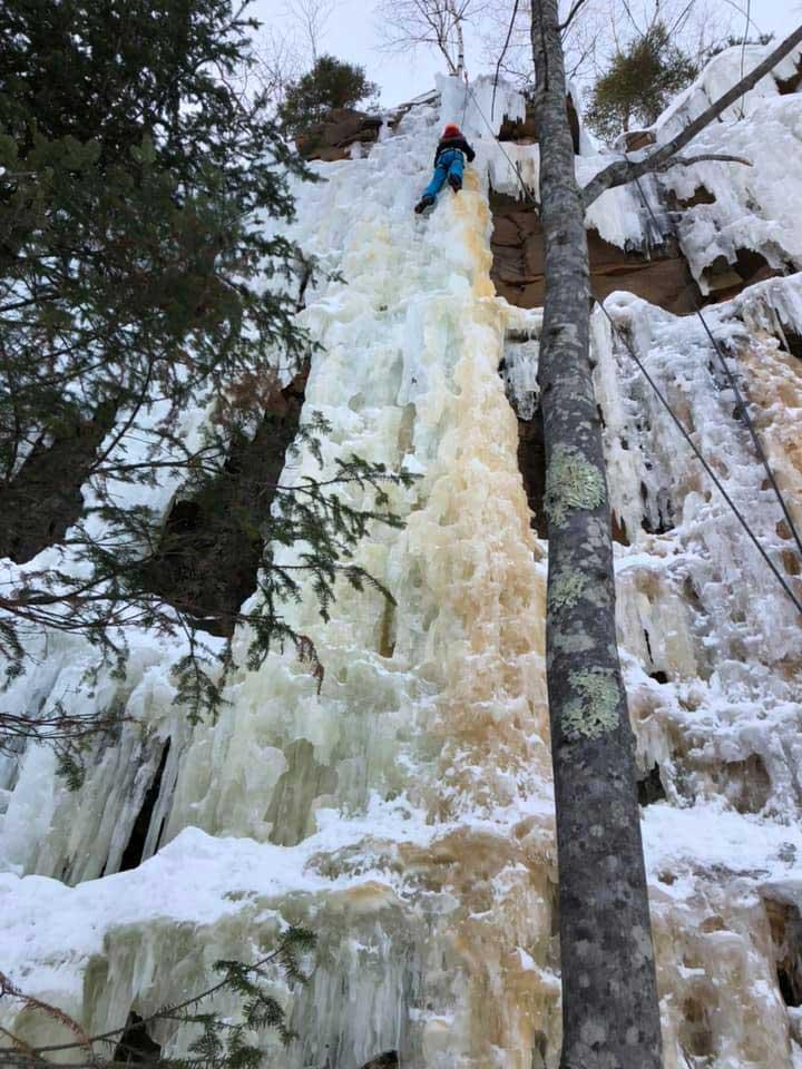 Wide angle shot of a Girl Scout climbing a frozen waterfall.