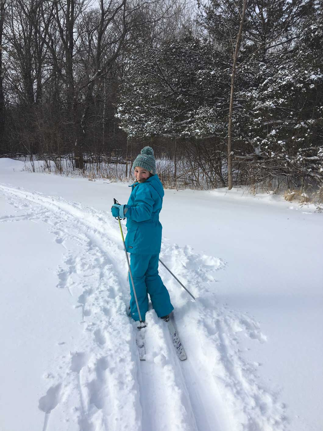 A junior Girl Scout cross country skiing.