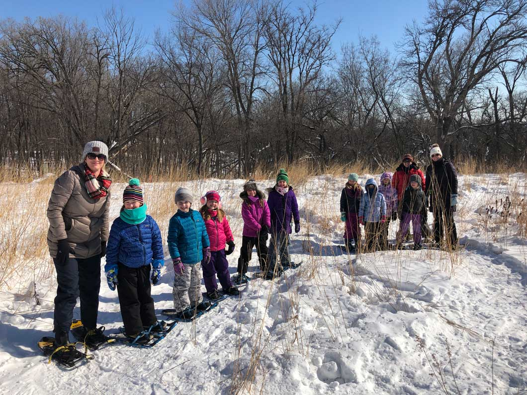 Brownie Girl Scout troop of nine girls and three adult volunteers stop to pose for a picture while snow shoeing.