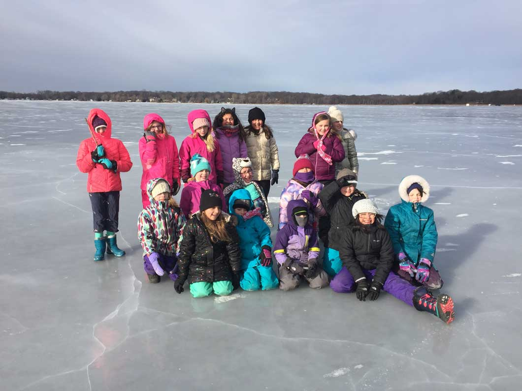 Girl Scout Troop 18102 posing for a picture in the middle of a frozen lake.