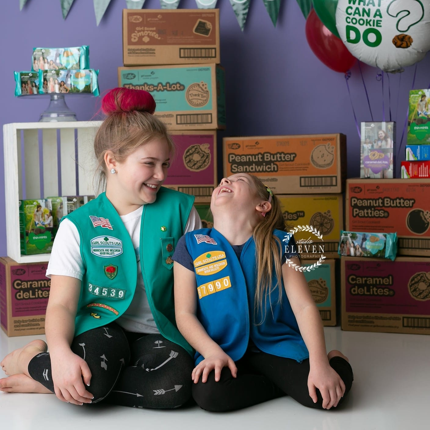 Two girl scouts sisters laughing candidly in front of their cookie packages.