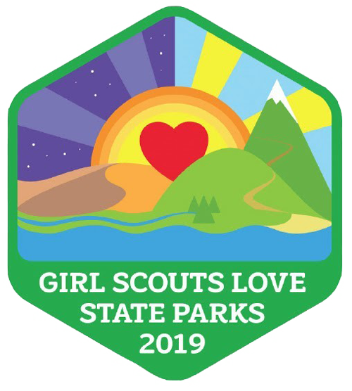 Green hexagon shaped patch containing landscape scene with a large red heart inside a sunset. Includes text Girl Scouts Love State Parks 2019