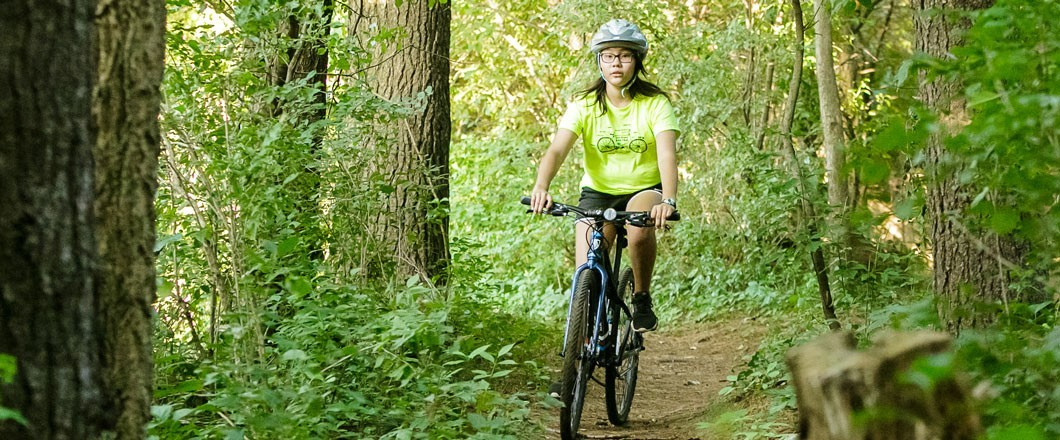 Girl Scout wearing bright yellow t-shirt riding a mountain bike through the woods.