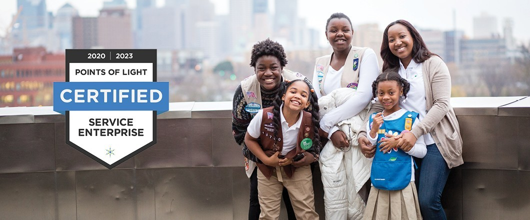 Girl Scout Troop hugging and smiling on Museum Balcony with graphic, 2020 | 2023 Points of Light Certified Service Enterprise