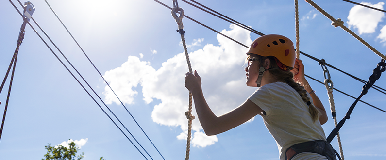 Girl scaling outdoor ropes course.