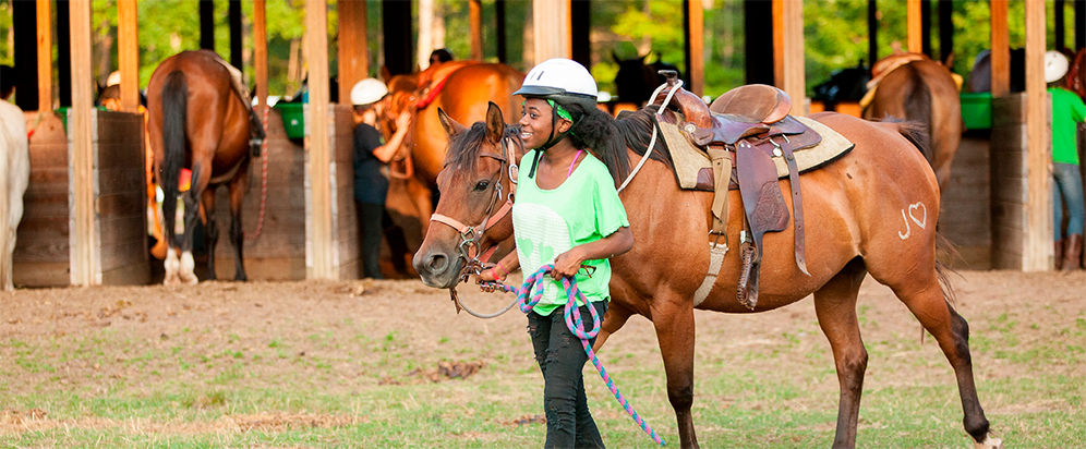 Girl Scout Guiding a Horse at Camp