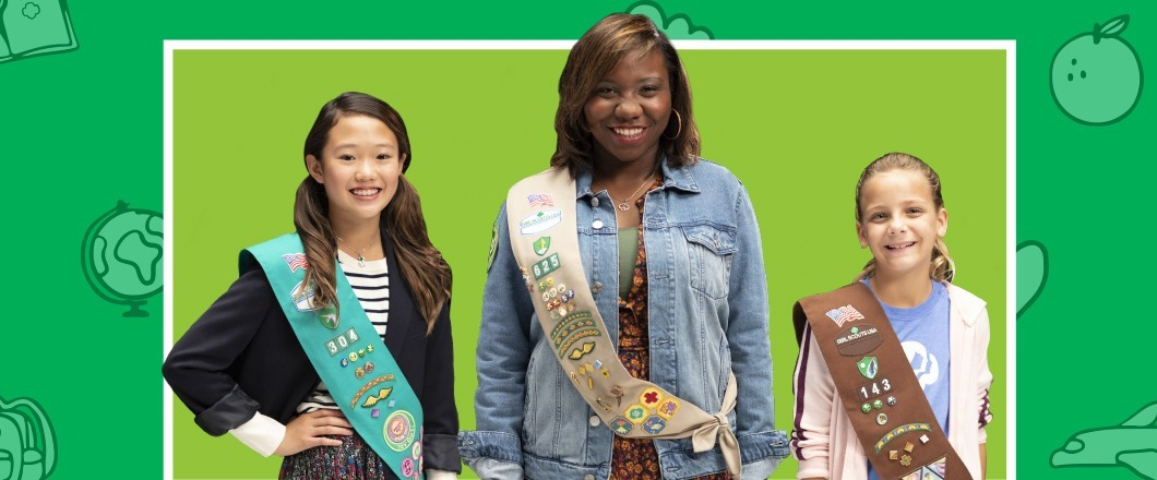Three Girl Scout members posing with their sashes full of badges