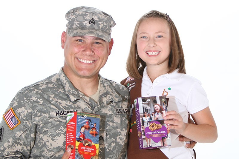 Girl Scout and military service member holding Girl Scout Cookie boxes