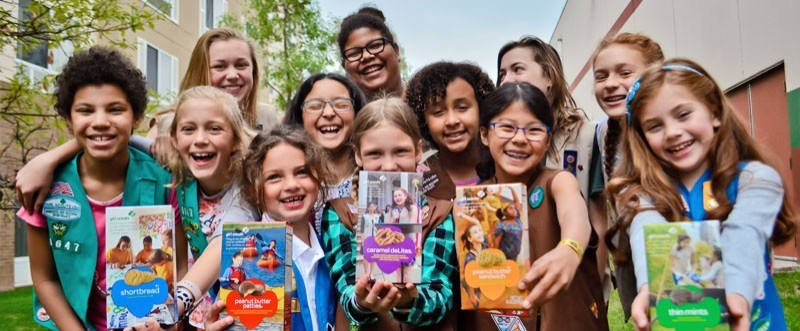 Girls Holding Boxes of Girl Scout Cookies
